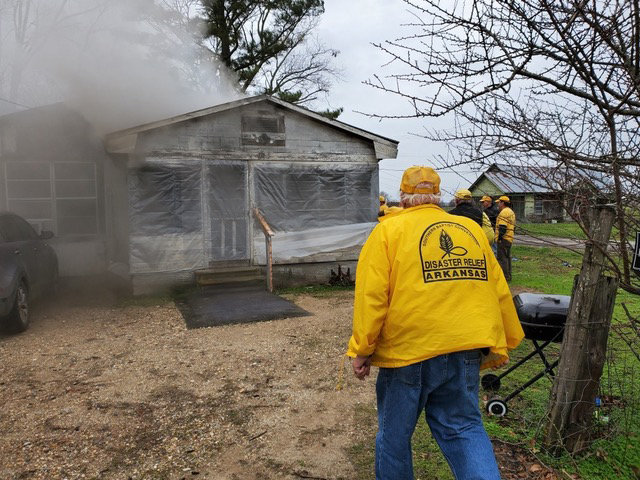 Arkansas Baptist Disaster Relief volunteers were repairing a roof damaged by recent tornadoes when they saw smoke rising from a house nearby. When a neighbor told them two elderly women were likely inside, the volunteers entered the house to find and remove the victims. (Submitted photo)