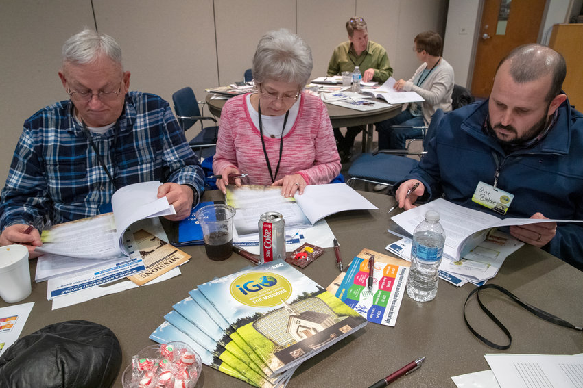 Participants at the iGo Workshop in Louisville pore over new materials designed to help churches evaluate and develop missions strategies. From left are Tony Callan and his wife, Pat, of Glencoe Baptist Church and Cory Bledsoe, a Kentucky MSC missionary at Re:Center Ministries in Louisville. Pat Callan serves as vice president of Kentucky Woman's Missionary Union and Ten Mile Baptist Association's WMU director. (Kentucky Today/Robin Cornetet)