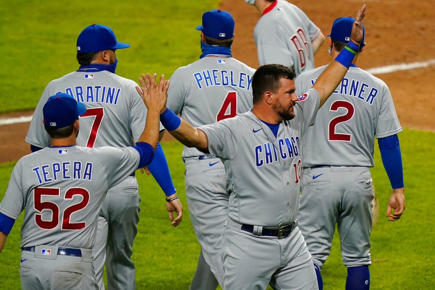 Chicago Cubs' Kyle Schwarber (12) celebrates with teammates after the Cubs defeated the Cincinnati Reds 8-7 in a baseball game in Cincinnati, Monday, July 27, 2020. (AP Photo/Bryan Woolston)