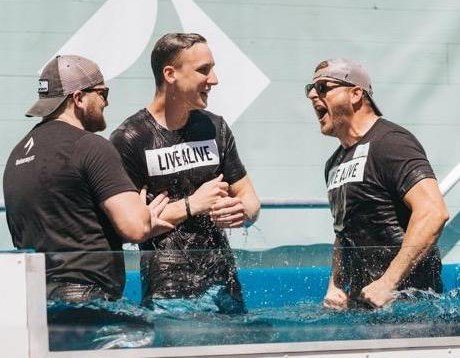 New believer Jordan Harris (center) celebrates his baptism at the Journey Church with Luke Wycuff (left), pastor of Journey's Orange City, Fla., location, and Tom Wycuff, worship team member. (Submitted photo)