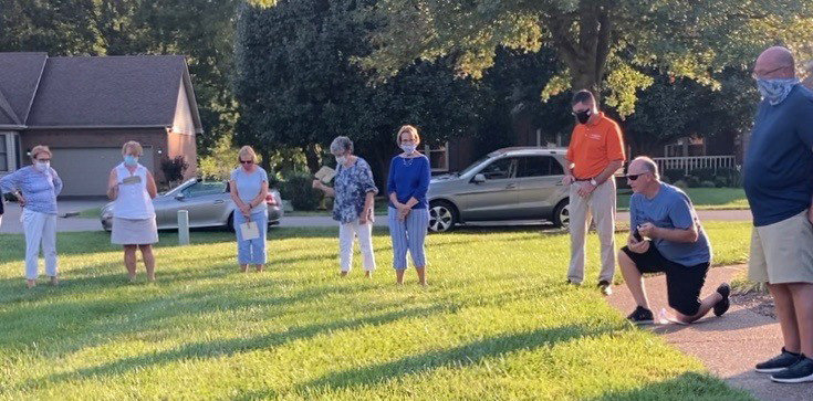 Several members of New Friendship Baptist Church in Auburn pray around the home of pastor Barry Raley, who had COVID-19. BELOW, photos of members praying.