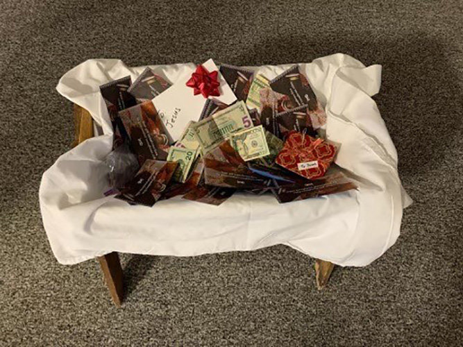 "Ekron Baptist Church in Brandenburg set a goal of $8,500 for the Lottie Moon offering and have more than doubled it with $19,200. Members put money in a manager as a ""gift for Jesus"" following a Sunday morning program. (Submitted photos)"