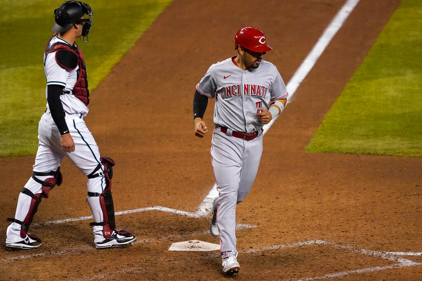 Cincinnati Reds' Eugenio Suarez (7) scores on a base hit by Tucker Barnhart during the 10th inning of a baseball game as Arizona Diamondbacks catcher Carson Kelly looks away, Friday, April 9, 2021, in Phoenix. (AP Photo/Matt York)