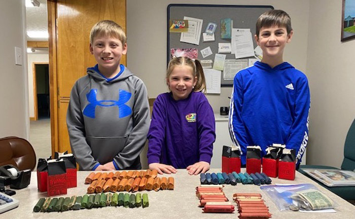 Cason Stinnett, Kinsley Stinnett and Beau Naylo display the barn-shaped coin banks they created as part of a mission project at New Middletown Baptist Church in Tennessee.