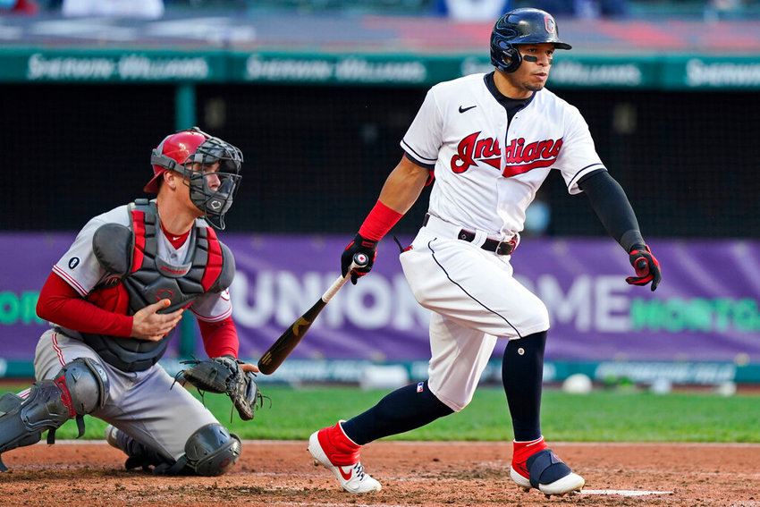 Cleveland Indians' Cesar Hernandez watches his ball after hitting a three-run triple in the fourth inning of a baseball game against the Cincinnati Reds, Saturday, May 8, 2021, in Cleveland. Cincinnati Reds catcher Tyler Stephenson watches. (AP Photo/Tony Dejak)