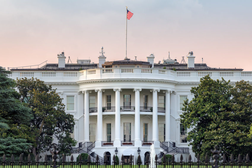 The White House in Washington DC with American flag on sunset sky at summer sunset.