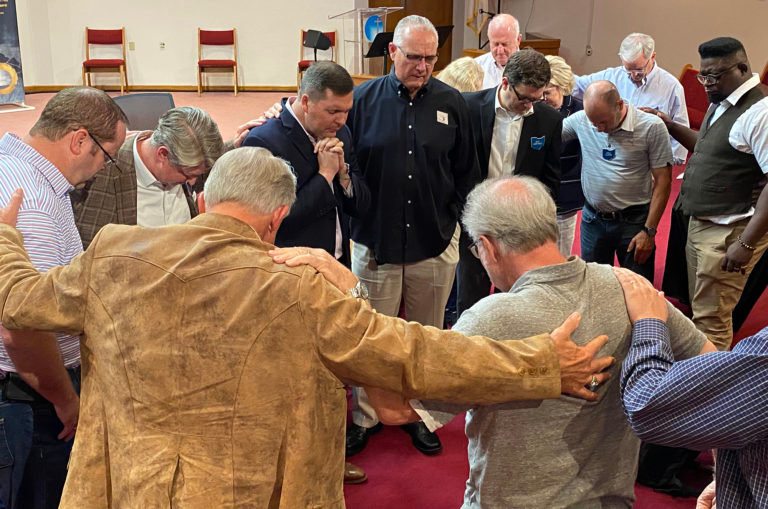 Members of the SCBO's Mission Council gather around Jeremy Westbrook, the state convention's new executive director, to pray.