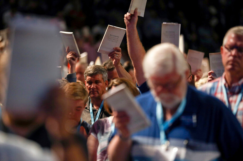 In this Wednesday, June 12, 2019 file photo, Bill Golden, and thousands of others, hold up copies of a training handbook related to sexual abuse within Southern Baptist churches during a speech by SBC President J. D. Greear on the second day of the SBC's annual meeting in Birmingham, Ala. As Southern Baptists prepare for their biggest annual meeting in more than a quarter-century in June 2021, accusations that leaders have shielded churches from claims of sexual abuse and simmering tensions around race threaten to once again mire the nation's largest Protestant denomination in a conflict that can look more political than theological. ( Jon Shapley/Houston Chronicle via AP, File)
