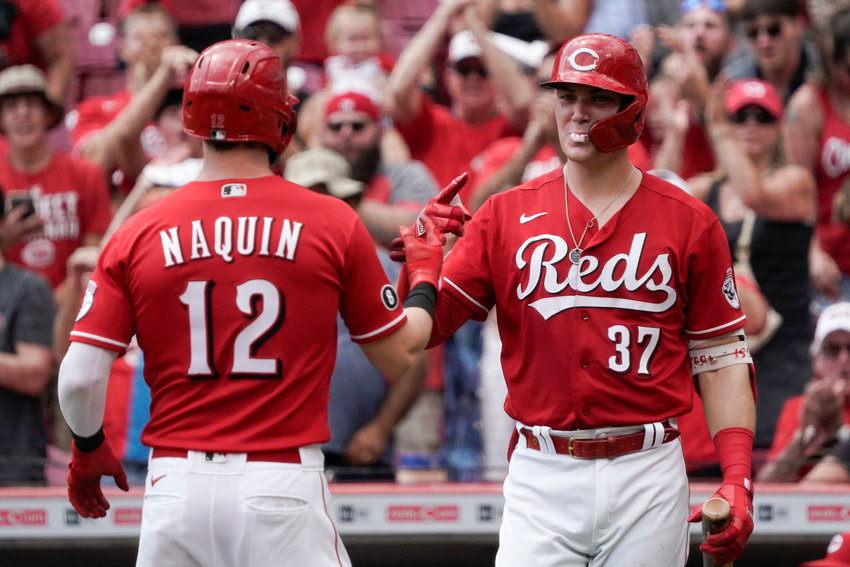 Cincinnati Reds' Tyler Naquin (12) celebrates with Tyler Stephenson (37) after hitting a solo home run during the first inning of a baseball game against the Miami Marlins Sunday, Aug. 22, 2021, in Cincinnati. (AP Photo/Jeff Dean)
