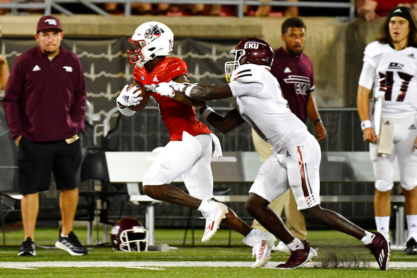 Louisville wide receiver Ahmari Huggins-Bruce (9) runs from the grasp of Eatern Kentucky defensive back Joseph Sayles (11) during the second half of an NCAA college football game in Louisville, Ky., Saturday, Sept. 11, 2021.Louisville won 30-3. (AP Photo/Timothy D. Easley)