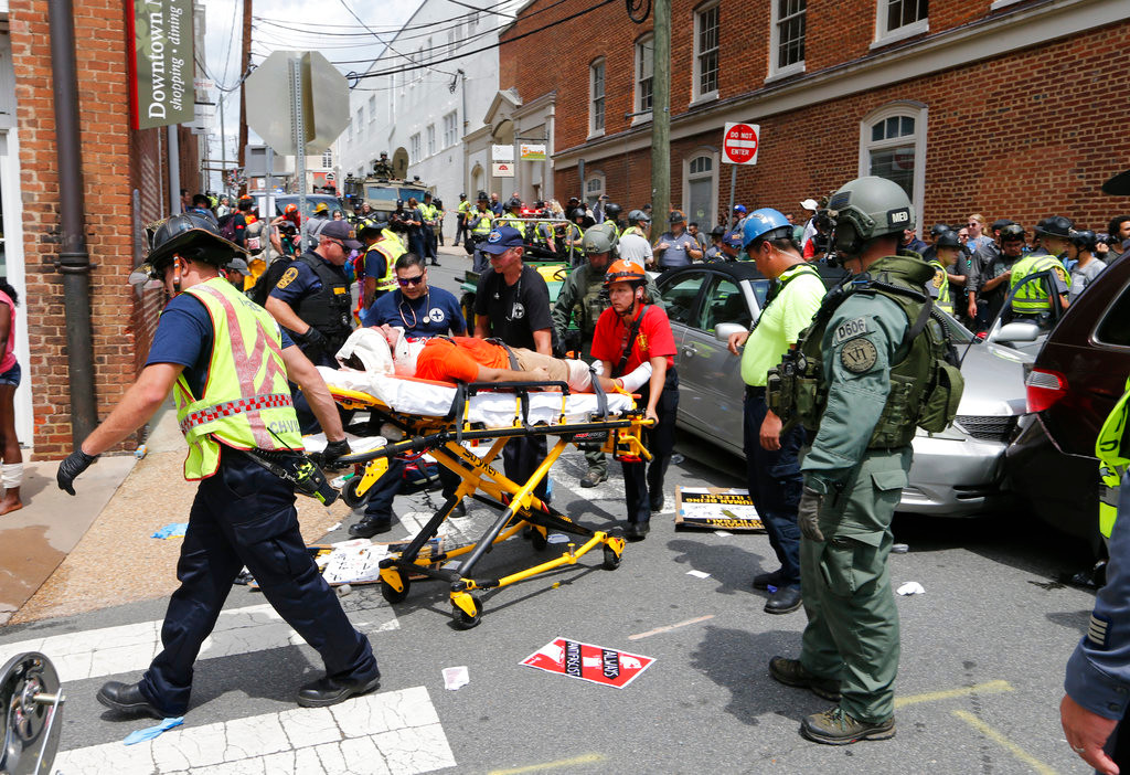 Rescue personnel help injured people after a car ran into a large group of protesters after an white nationalist rally in Charlottesville, Va., Saturday, Aug. 12, 2017.  The nationalists were holding the rally to protest plans by the city of Charlottesville to remove a statue of Confederate Gen. Robert E. Lee. There were several hundred protesters marching in a long line when the car drove into a group of them. (AP Photo/Steve Helber)