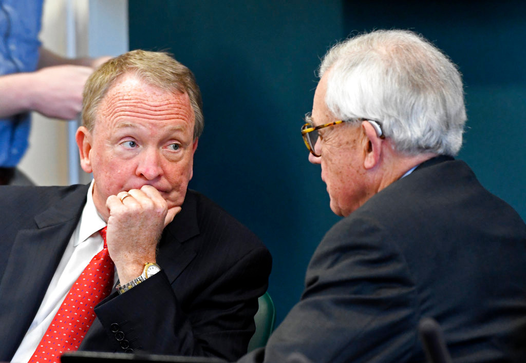 Acting University of Louisville President Greg Postel, left, speaks with Board of Trustees Chairman J. David Grissom before the start of the Board of Trustees meeting, Wednesday, Oct. 18, 2017, in Louisville, Ky. The board discussed whether to terminate athletic director Tom Jurich. (AP Photo/Timothy D. Easley)