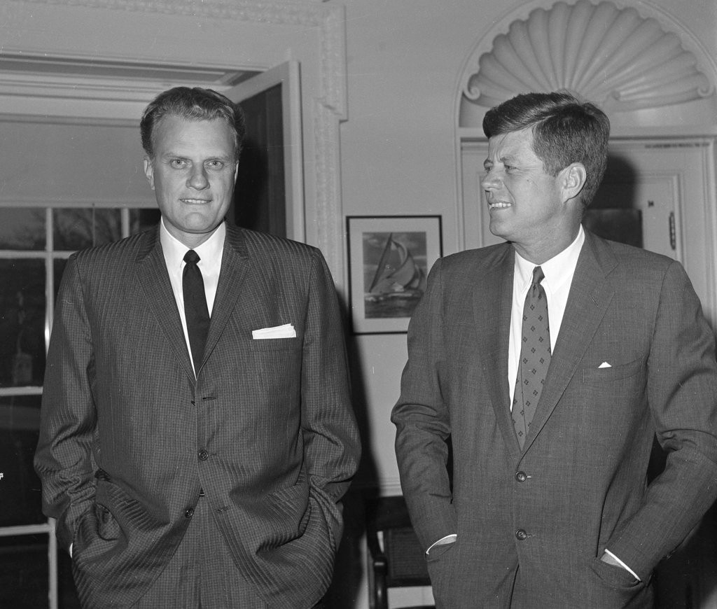 FILE - In this Dec. 12, 1961 file photo,  Evangelist Billy Graham, left, talks with President John F. Kennedy during a call at the the White House in Washington.   Graham, who transformed American religious life through his preaching and activism, becoming a counselor to presidents and the most widely heard Christian evangelist in history, has died. Spokesman Mark DeMoss says Graham, who long suffered from cancer, pneumonia and other ailments, died at his home in North Carolina on Wednesday, Feb. 21, 2018. He was 99. (AP Photo, File)