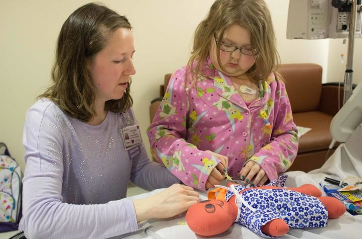 Child Life Specialist Ashley Rapske helps young Shannon understand how IVs work by practicing on a doll. (UK HealthCare photo)