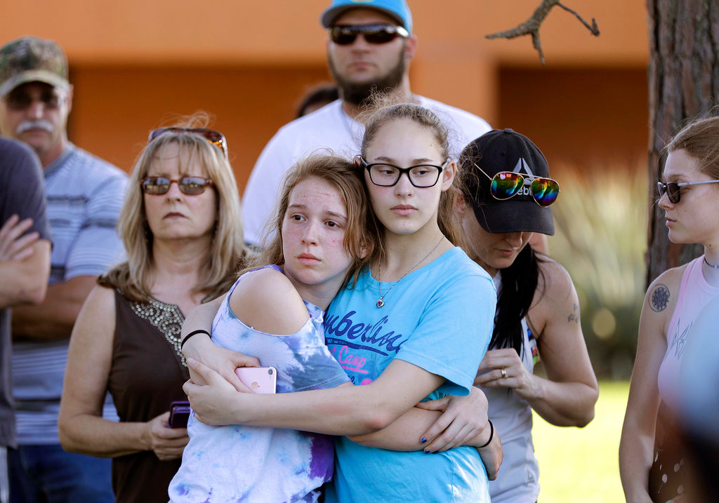 FILE - In this Friday, May 18, 2018, file photo, mourners wait for the start of a prayer vigil following a deadly shooting at Santa Fe High School in Santa Fe, Texas. If you want to know where mass school shootings are most likely to occur, look no farther than small-town and suburban America. (AP Photo/David J. Phillip, File)