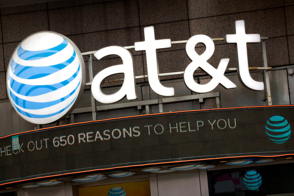 FILE - In this Monday, Oct. 24, 2016, file photo, the AT&T logo is positioned above one of its retail stores, in New York.  The fate of the AT&T-Time Warner merger, a massive media deal opposed by the government that could shape how much consumers pay for streaming TV and movies, rests in the hands of a federal judge.  U.S. District Judge Richard Leon is expected to announce in court Tuesday, June 12, 2018  his decision in the biggest antitrust trial in years.  (AP Photo/Mark Lennihan, File)