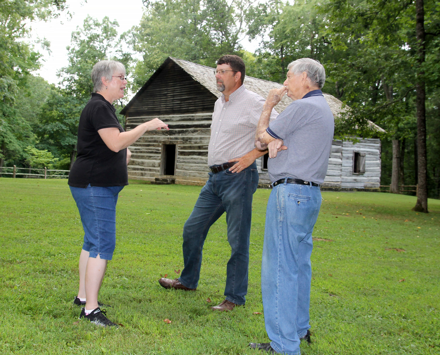 Old Mulkey Meetinghouse State Historic Site park manager Sheila Jobe, left, talks with Pastor Larry Lowe, center, and Associational Mission Strategist John Jordan outside a building that once was home to Mill Creek Baptist Church.  (Kentucky Today/Roger Alford)