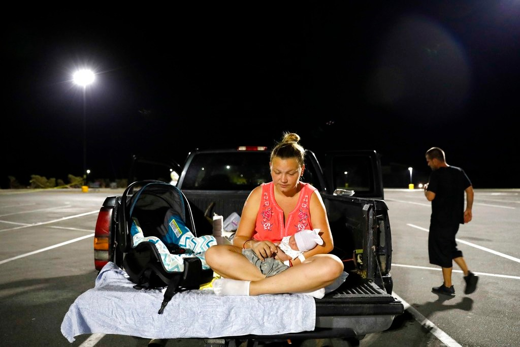 In this Monday, Oct. 15, 2018 file photo, Lorrainda Smith sits with her 2-day-old son, Luke, as she contemplates with her husband, Wilmer Capps, right, sleeping in their truck in a parking lot after their home was damaged from Hurricane Michael and they were told a nearby shelter was closed, in Panama City, Fla. Wilmer Capps says he and wife Lorrainda Smith had no choice but to camp out at the store the night their son Luke was released from an Alabama hospital because their home in Panama City, Florida, was badly damaged by the storm. (AP Photo/David Goldman, File)