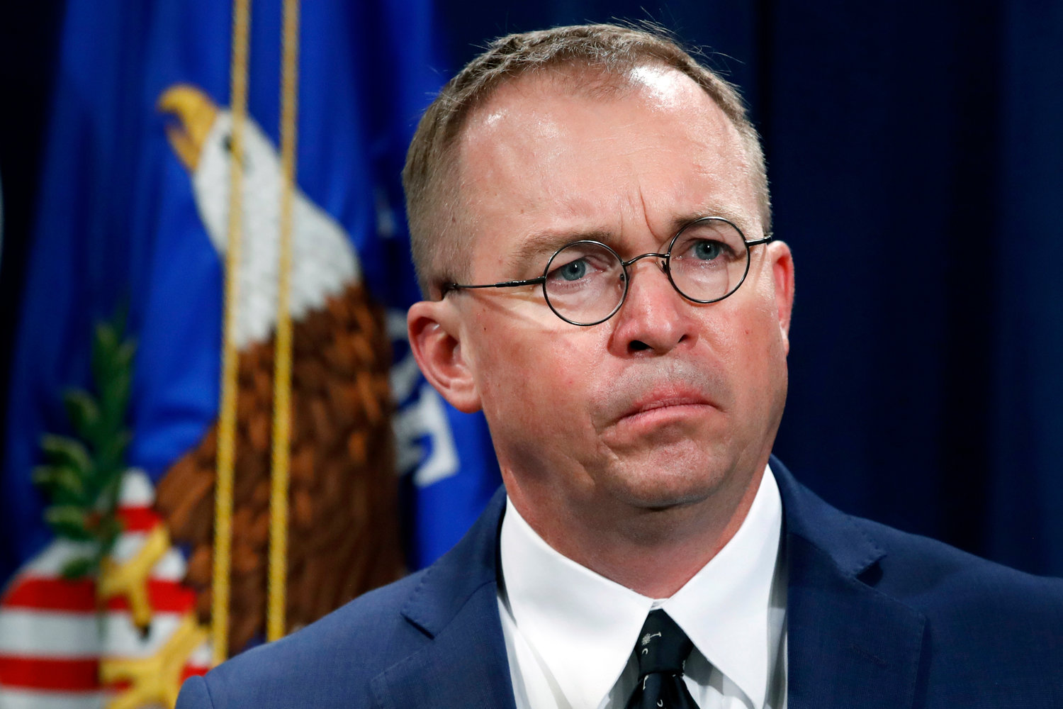 In this July 11, 2018, file photo Mick Mulvaney, acting director of the Consumer Financial Protection Bureau (CFPB), and Director of the Office of Management, listens during a news conference at the Department of Justice in Washington. White House Acting Chief of Staff Mick Mulvaney isn't setting any lofty goals for this weekend's meeting with a bipartisan mix of legislators at Camp David, but he is trying to build relationships across the aisle. (AP Photo/Jacquelyn Martin, File)