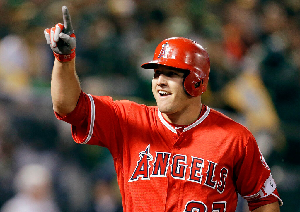 In this April 3, 2017, file photo, Los Angeles Angels' Mike Trout celebrates after hitting a two-run home run off Oakland Athletics' Kendall Graveman in the third inning of a baseball game in Oakland, Calif. A person familiar with the negotiations tells The Associated Press Tuesday, March 19, 2019, that Trout and the Angels are close to finalizing a record $432 million, 12-year contract that would shatter the record for the largest deal in North American sports history. (AP Photo/Ben Margot, File)
