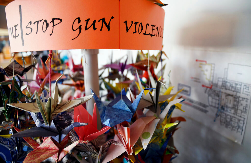 In this March 23, 2019, file photo, origami cranes, a symbol of peace, hang in the Columbine High School library in Littleton, Colo., near where several survivors and family members of the victims gathered to speak about the upcoming 20th anniversary of the April 20, 1999, shooting. In the two decades since the Columbine High School massacre, therapists still struggle with how to help people cope. (AP Photo/Thomas Peipert, File)
