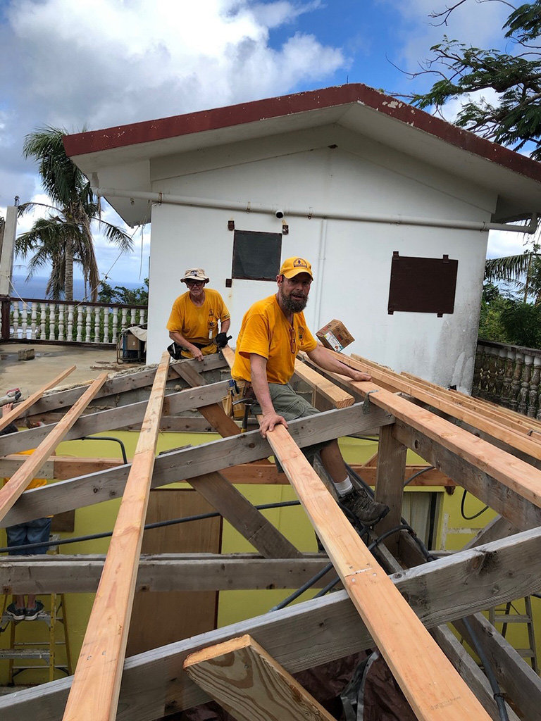 Two Kentucky Disaster Relief workers put up the braces before putting on a metal roof on homes in Saipan.