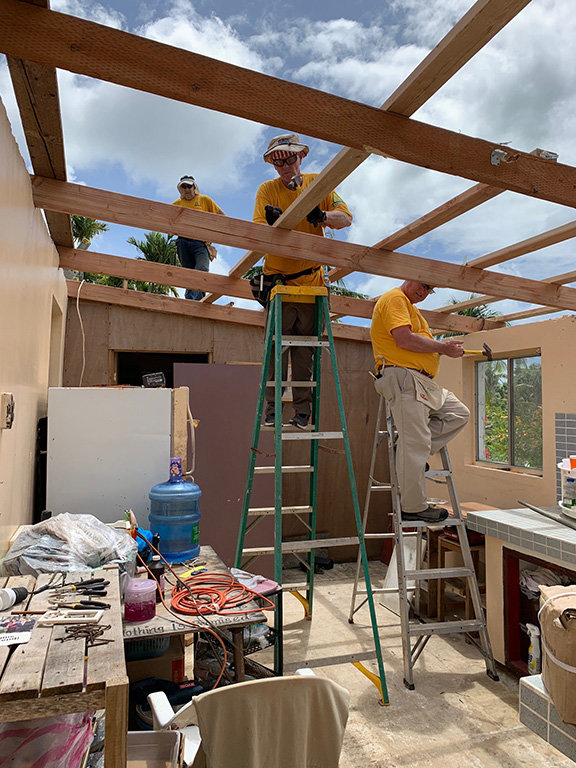 Kentucky Disaster Relief workers hammer on braces that will hold up a metal roof in typhoon-torn Saipan. (Submitted photo)