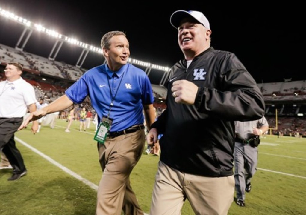 Mitch Barnhart and Mark Stoops are taking careful steps as schools re-open to allow athletes back on campus for voluntary workouts next month. (UK Athletics Photo)