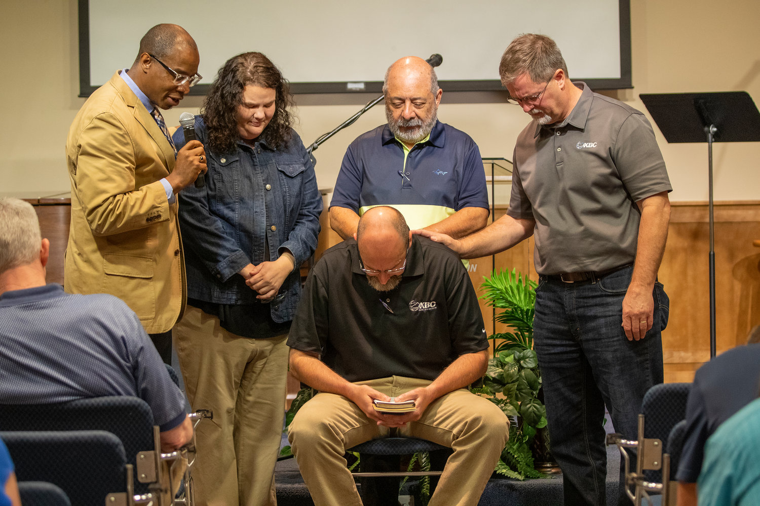 Kentucky Baptist Convention Co-interim Executive Director Curtis Woods (left) leads Mission Board staff in prayer after the announcement that Evangelism Team Leader Todd Gray (seated) was selected as the candidate to become the next executive director-treasurer.  Mission Board staff learned about Gray's selection via video from Search Committee Chairman Wes Fowler on Wednesday, July 17, 2019.  The KBC Mission Board will meet July 25 and vote on whether to confirm Gray. Also pictured are (second left) Evangelism Team Ministry Assistant DeAnna Terry, Church Planting Strategist Carlos De la Barra, and Church Evangelism Strategist Andy McDonald. (Kentucky Today/Robin Cornetet)