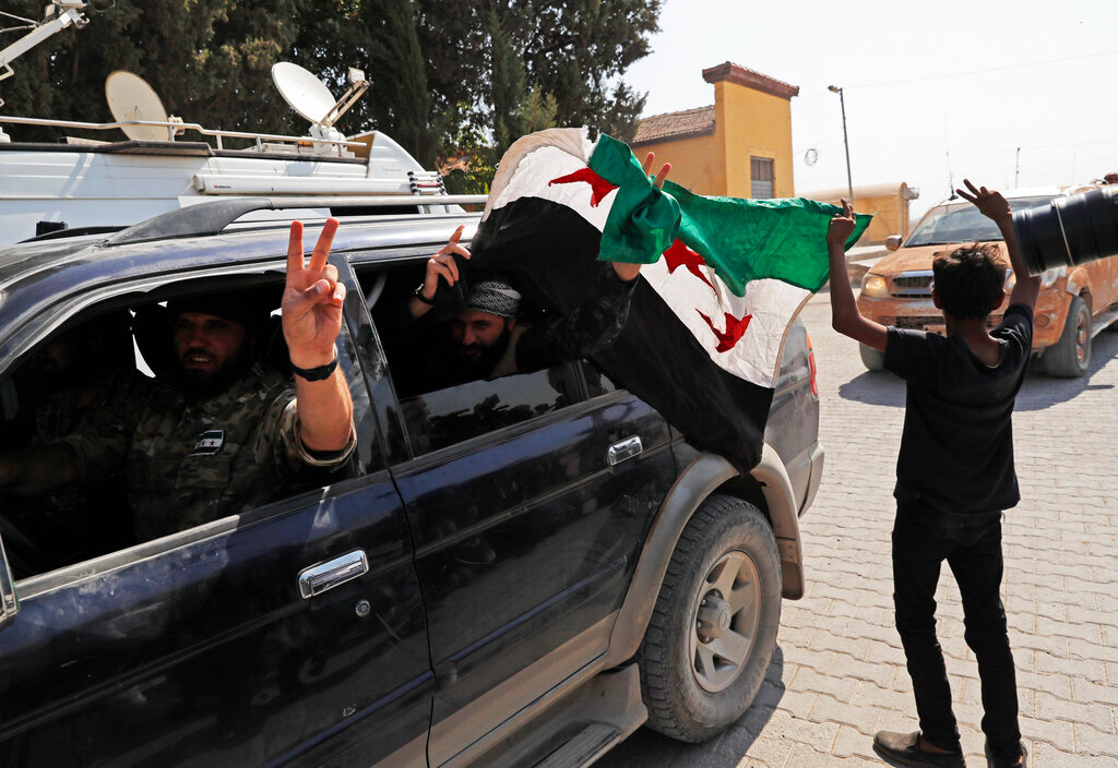 Members of Turkey-backed Syrian National Army (former FSA) flash the V-sign as they drive back to Turkey after they went in for some time on inspection according to the Turkish police entourage in the same area at the border between Turkey and Syria, in Akcakale, Sanliurfa province, southeastern Turkey, Wednesday, Oct. 9, 2019. Turkish President Recep Tayyip Erdogan has long threatened to send troops into northeastern Syria to clear the border region of Syrian Kurdish fighters whom Turkey considers a serious security threat. (AP Photo/Lefteris Pitarakis)
