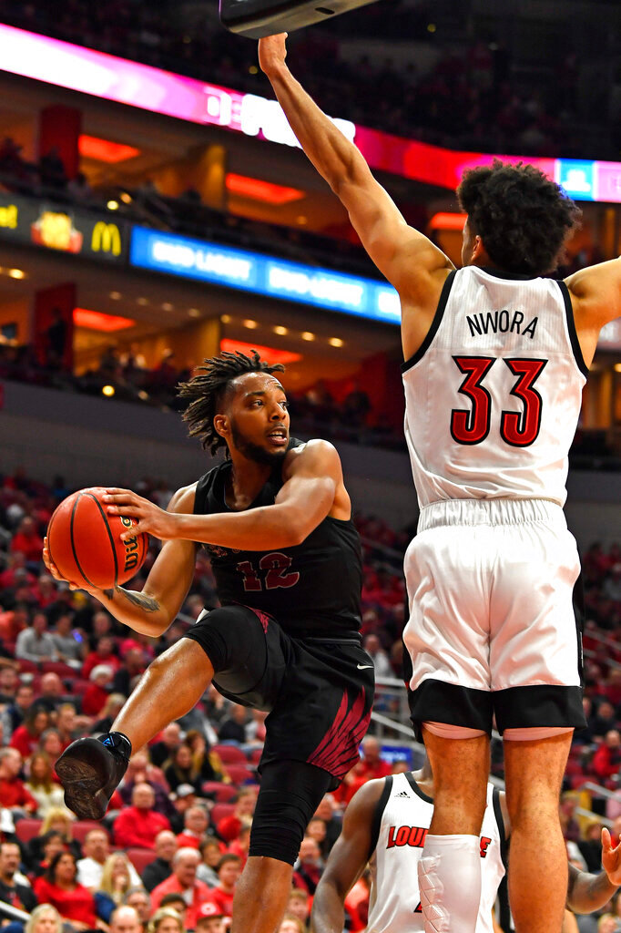 North Carolina Central guard Jordan Perkins (12) loos to pass around the defense of Louisville forward Jordan Nwora (33) during the first half of an NCAA college basketball game in Louisville, Ky., Sunday, Nov. 17, 2019. (AP Photo/Timothy D. Easley)
