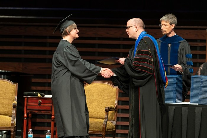 Southwestern Theological Seminary President Adam Greenway presents a degree to Susan K. Rainey, who was the 10,000th female graduate in its 111-year history. (Southwestern Theological Seminary photo)