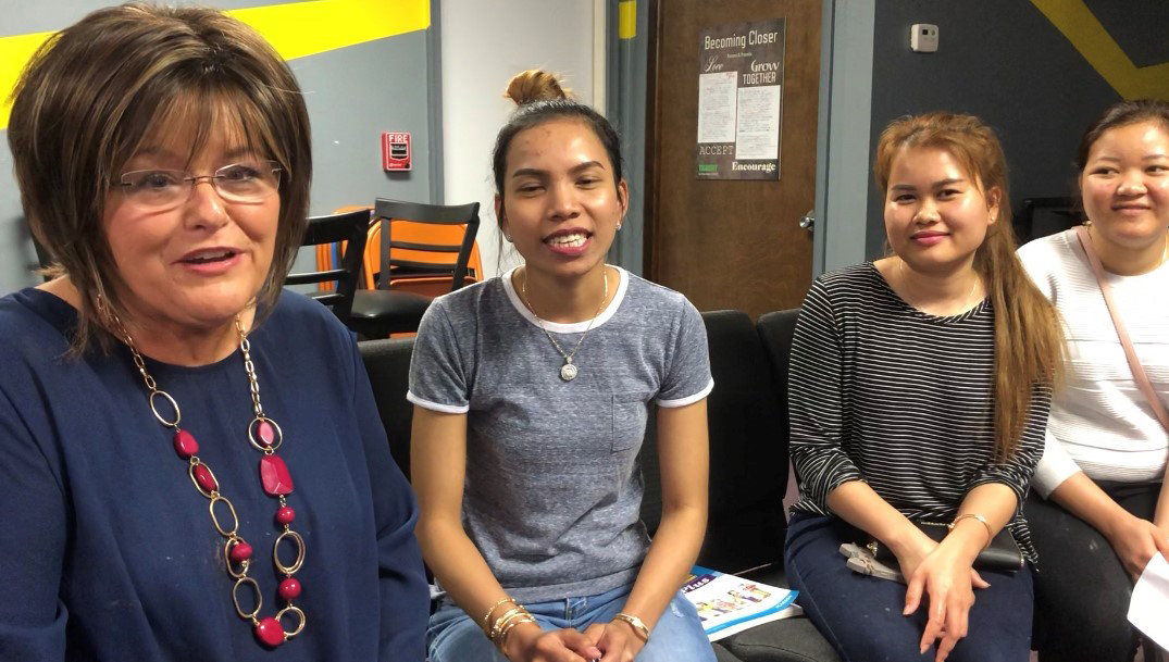 Debbie Cole, one of the coordinators of the English as a Second Language program at Unity Baptist Church in Ashland, Ky., sits with three of the international students. (Kentucky Today/Mark Maynard)