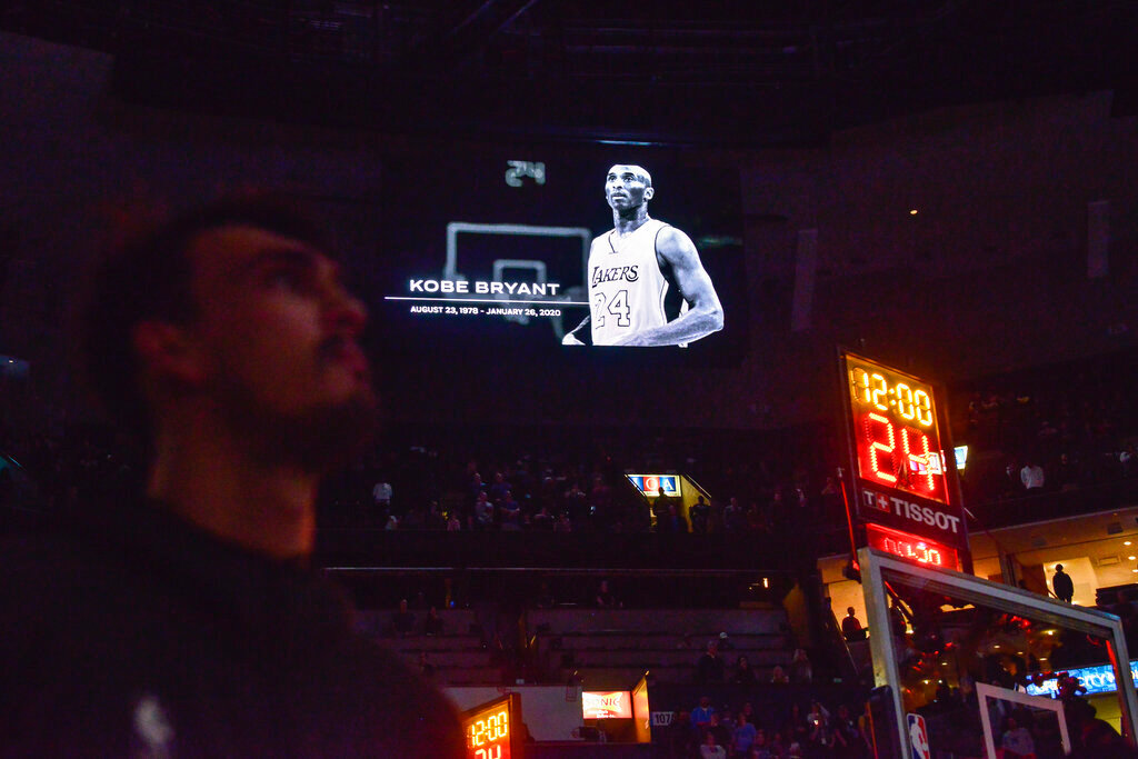 Players and fans observe a moment of silence for former NBA player Kobe Bryant before a basketball game between the Phoenix Suns and the Memphis Grizzlies, Sunday, Jan. 26, 2020, in Memphis, Tenn. Bryant died in a California helicopter crash Sunday. (AP Photo/Brandon Dill)