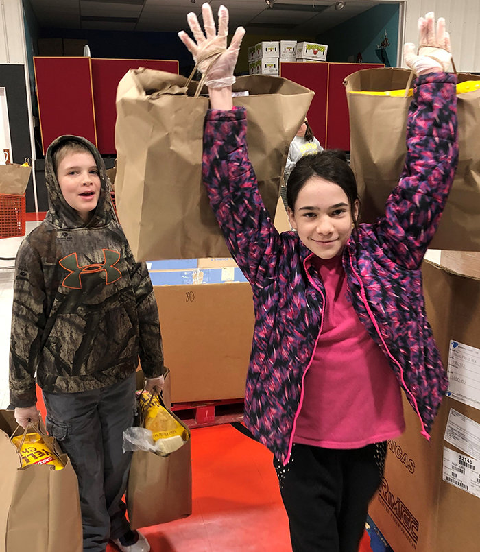Tara Barker holds up two bags of food over her head as little brother Seth watches at the May's Lick food pantry. (Kentucky Today/Ray Schaefer)