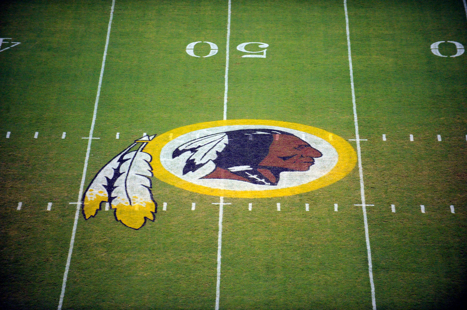 "In this Aug. 28, 2009 file photo, the Washington Redskins logo is shown on the field before the start of a preseason NFL football game against the New England Patriots in Landover, Md. The Washington Redskins are undergoing what the team calls a ""thorough review"" of the nickname. In a statement released Friday, July 3, 2020, the team says it has been talking to the NFL for weeks about the subject. Owner Dan Snyder says the process will include input from alumni, sponsors, the league, community and members of the organization. FedEx on Thursday called for the team to change its name, and Nike appeared to remove all Redskins gear from its online store. (AP Photo/Nick Wass, File)"