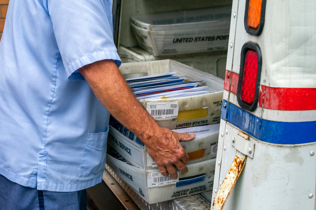 Letter carriers load mail trucks for deliveries at a U.S. Postal Service facility in McLean, Va., Friday, July 31, 2020. President Donal Trump has repeatedly raised unsubstantiated fears of fraud involving mail-in voting, which is expected to be more widely used in the November election out of concern for safety given the COVID-19 pandemic. (AP Photo/J. Scott Applewhite)