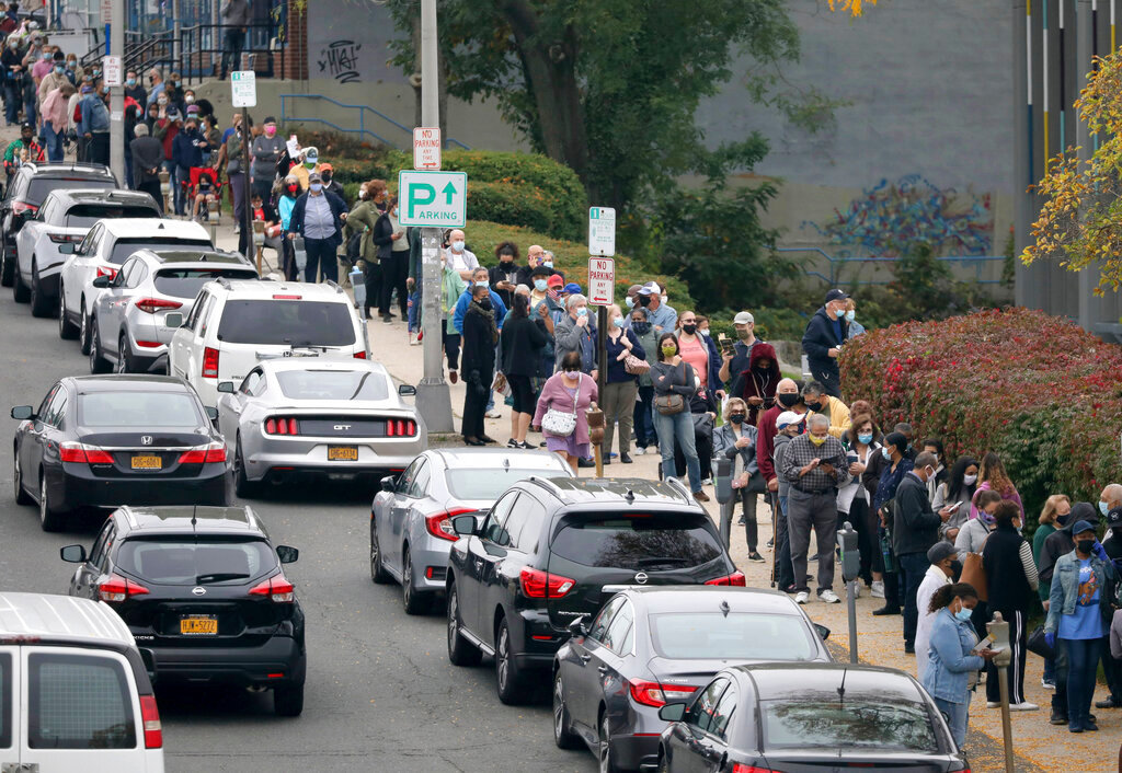 Voters line up in front of the Yonkers Public Library in Yonkers, N.Y., on Oct. 24, 2020 as  the first day of early voting in the presidential election begins across New York state. (Mark Vergari/The Journal News via AP)