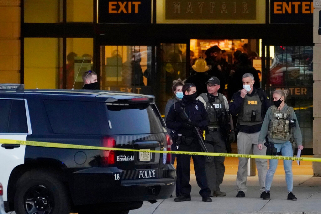FBI officials and police officials stand outside the Mayfair Mall, Friday, Nov. 20, 2020, in Wauwatosa, Wis. Multiple people were shot Friday afternoon at the Mayfair Mall in Wauwatosa, Wisconsin, and police are still searching for the shooter. (AP Photo/Nam Y. Huh)