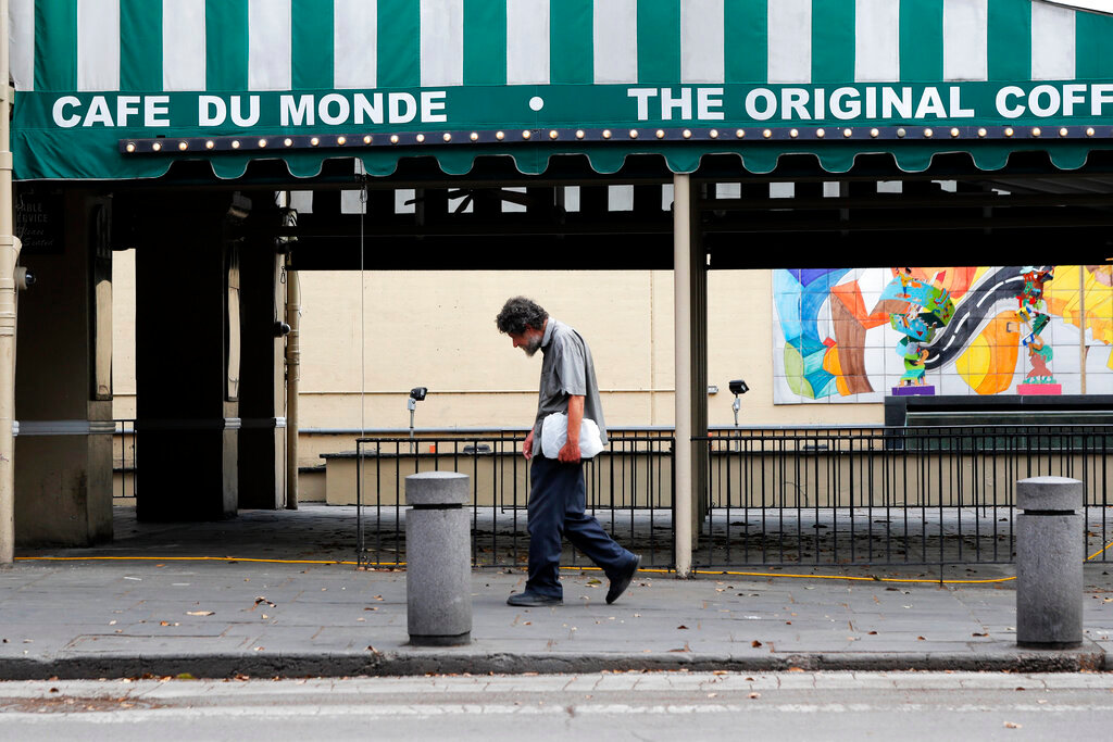 In this March 27, 2020, file photo, a man walks past the Cafe Du Monde restaurant, which was closed but has since reopened, in the French Quarter of New Orleans. President-elect Joe Biden will inherit a mangled U.S. economy, one that never fully healed from the coronavirus and could suffer again as new infections are climbing. The once robust recovery has shown signs of gasping after federal aid lapsed. Ten million remain jobless and more layoffs are becoming permanent. The Federal Reserve found that factory output dropped.  (AP Photo/Gerald Herbert, File)