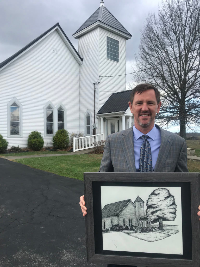 Dr. Paul Chitwood stands in front of South Fork Baptist Church in Owenton, Ky., with a print of the church.