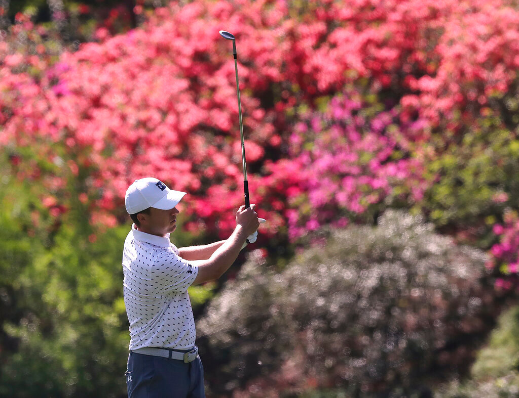 "The azaleas are beginning to pop as Jordan Spieth chips to the 13th green during his practice round for the Masters at Augusta National Golf Club on Tuesday, April 6, 2021, in Augusta.   ""Curtis Compton / Curtis.Compton@ajc.com"""