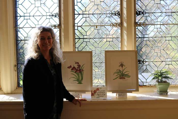 "Mireille Belajonas with her artwork, ""Miltonia Eleanor Ruby"" (left) and ""Paphiopedilum Jakob"" (right)."