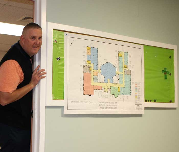 Bayport-Blue Point Library Director Michael Firestone stands beside the renovation plans for the former Ursuline Center. He is standing in the future children's wing.