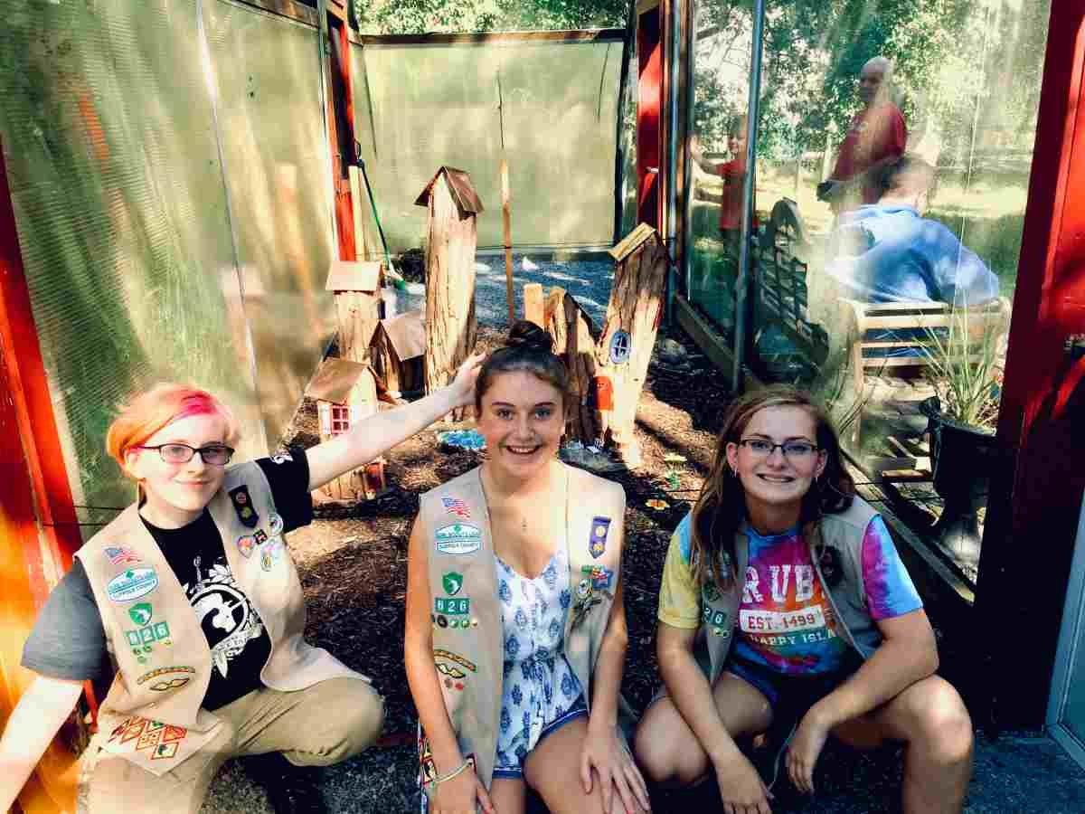 Pictured are Morgan Bissell, Kaylin Rutherig and Madison Smith in front of their fairy village, which took a few years to conceptualize and create, at Sweet Briar in Smithtown.