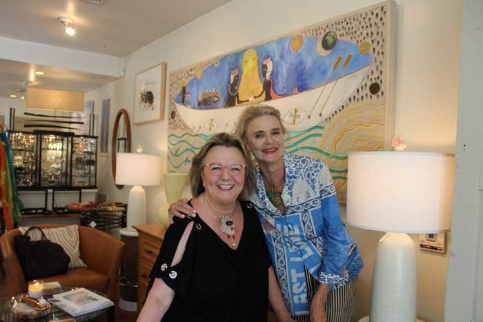 Cécile Defforey and Pamela Lerner in front of one of Defforey's fanciful paintings wearing Defforey's pendants.