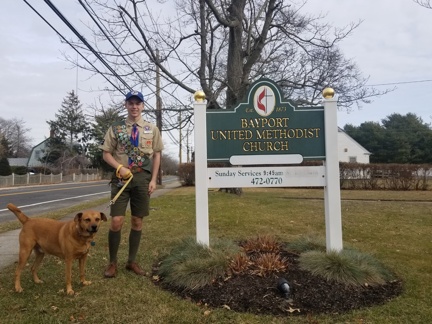 Recently named Eagle Scout, Frank Bollerman, 17, from Blue Point, poses with his loyal dog, Rocky, in front of the Bayport Methodist Church, where he completed his Eagle Scout project.