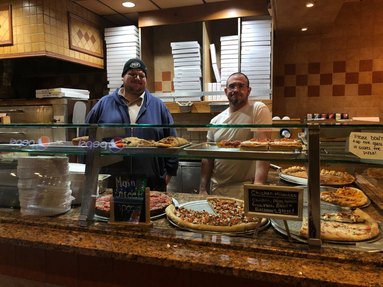 "Longtime employee ""Mackey"" stands behind the counter in his usual spot in Sayville Pizza with co-owner Chad Johnson. The pizza place is now officially for sale."