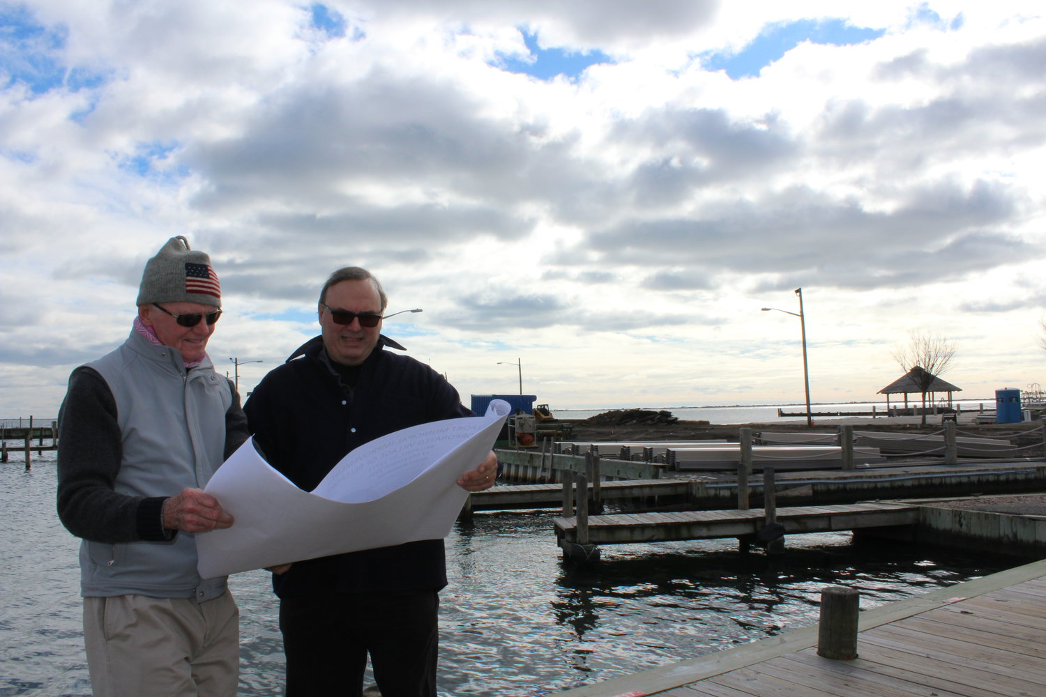 Bellport Mayor Ray Fell and Village Clerk John Kocay look over dock renovation plans that Terry Contracting will tackle.