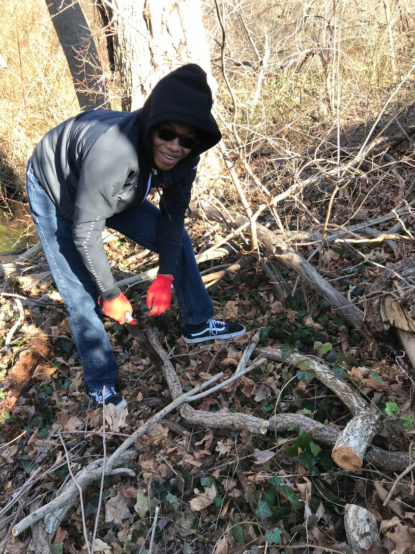 Brandon Martin, a member of First Baptist Church of Bay Shore, pulled weeds using gloves during the cleanup.